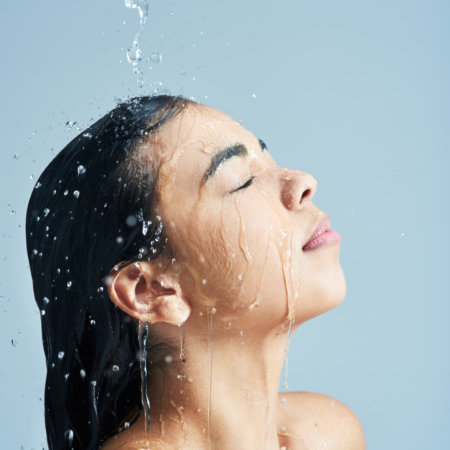 Shot of a young woman having a shower against a blue background